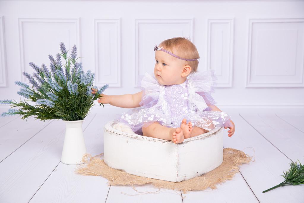 Maedchen sitzt in einer Herzschale und schaut sich einen Strauß Lavendel an, Kinderfotos, Blumen, Lavendel, Carina rosen, fotograf Lohmar