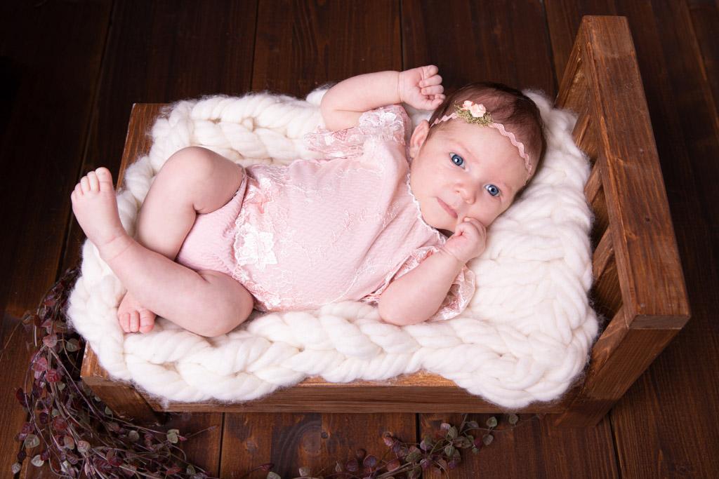 Mädchen liegt auf einem braunen Holzbett und schaut aufmerksam in die Kamera, Babyfotos bonn, carina rosen, fotografin overath
