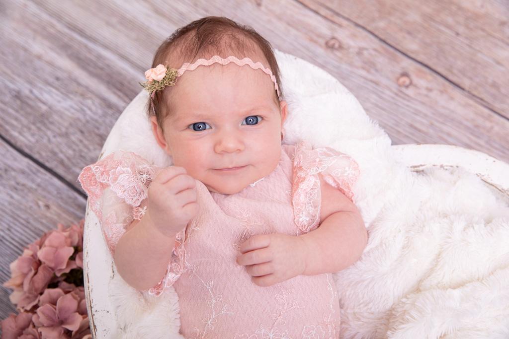 Baby Mädchen strahlt in die Kamera. sie trägt ein rosafarbenes outfit und ein passendes Haarband, carina rosen, fotograf in der nähe von bonn