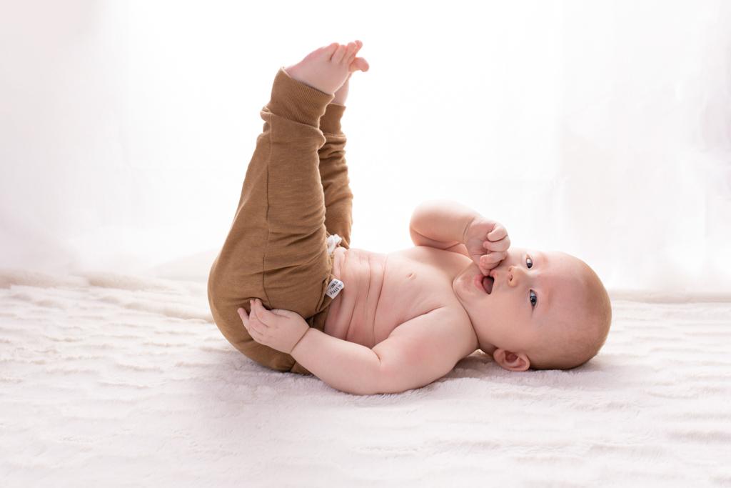 Junge mit brauner Hose liegt auf dem Boden und streckt die Beine hoch, carina rosen, fotografin nähe köln, babyfotos