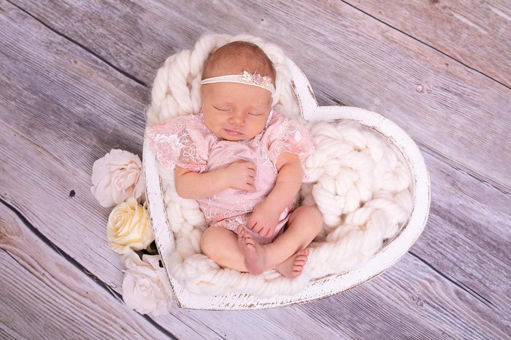 Neugeborenes Mädchen im rosa Outfit, schlafend in einer Herzschale. Babyshooting bei Carina Rosen Lohmar