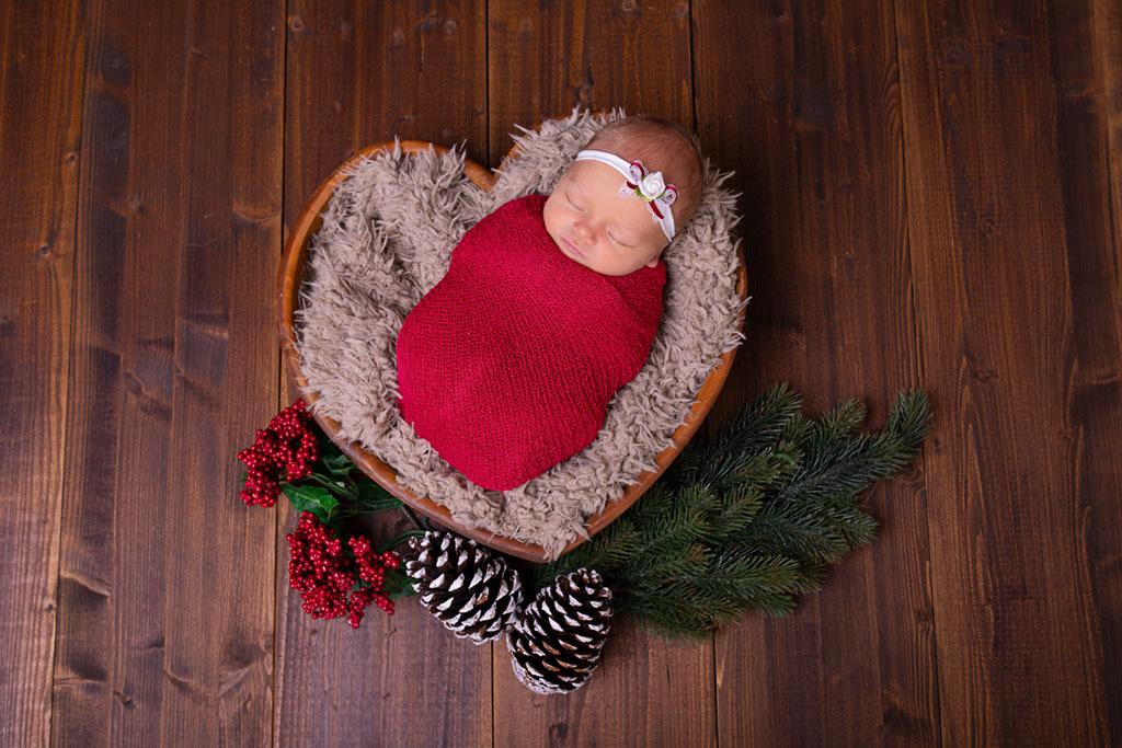 Baby in ein rotes Tuch gewickelt, liegt in einer Herzschale und träumt. Neugeborenenfotografie von Carina Rosen bei rösrath