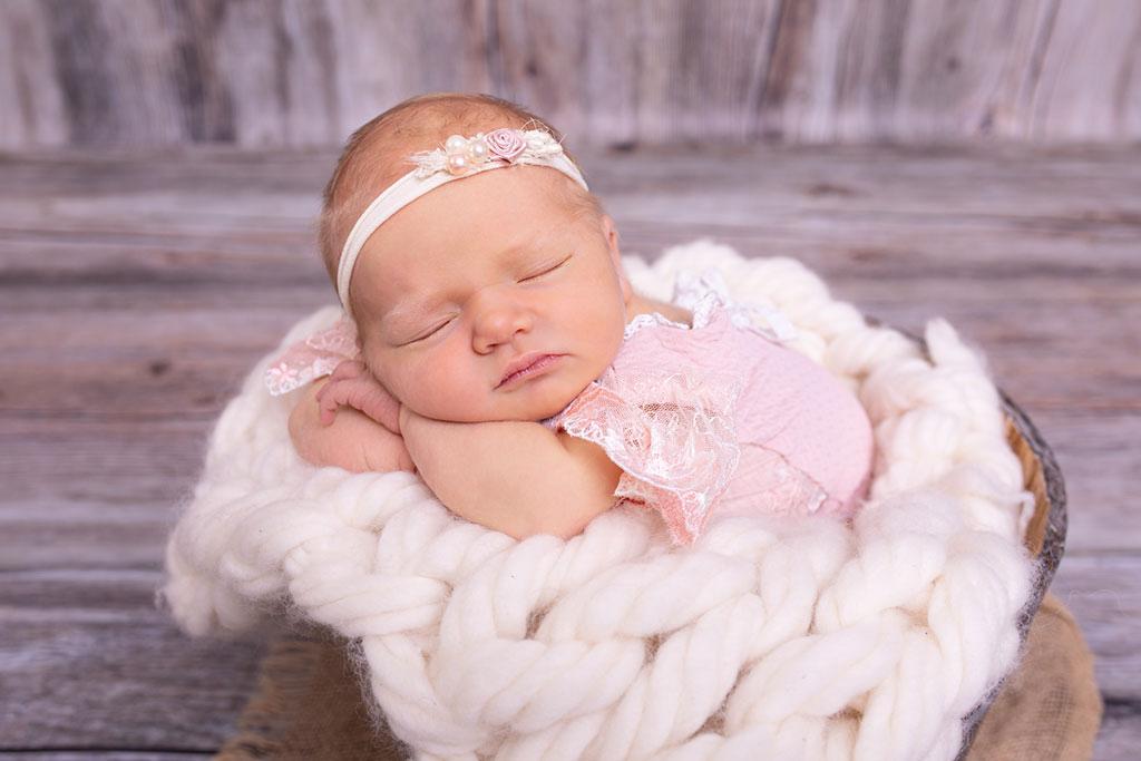 Neugeborene in rosa Outfit und schläft. Neugeborenenshooting bei Carina Rosen