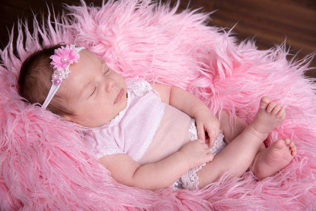 Baby liegt auf einem rosa Fell und schläft, babyshooting, babyfotos koeln, carina rosen, fotografin lohmar