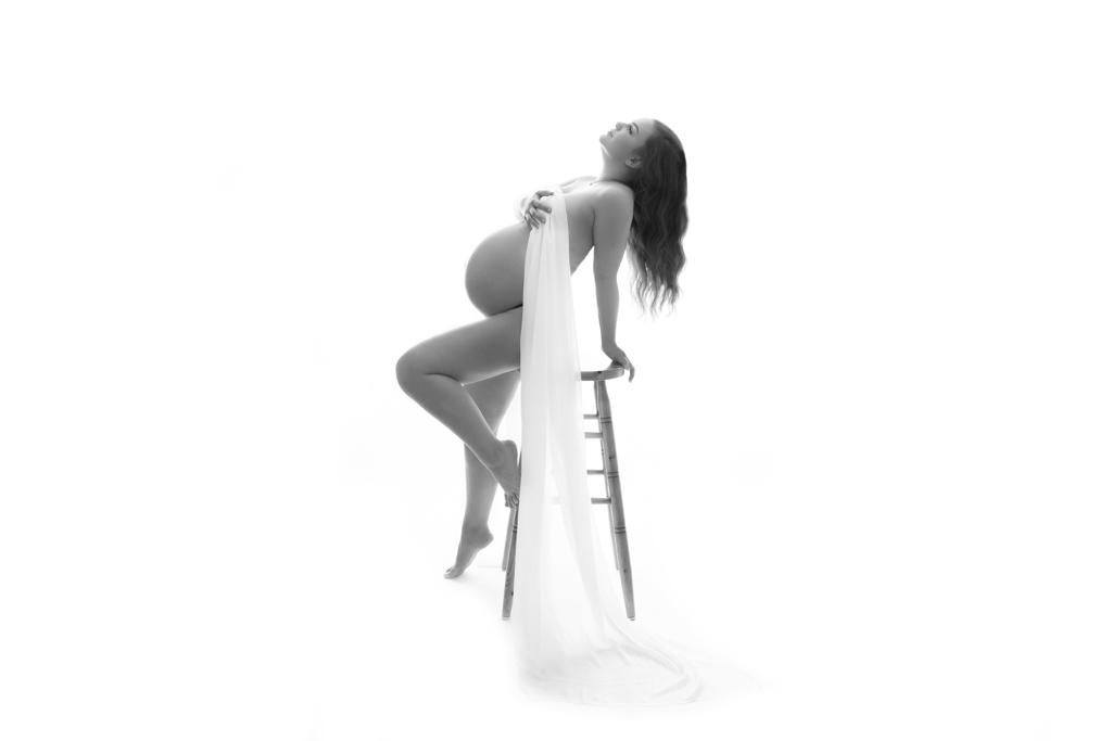Schwangere lehnt sich auf einen Hocker und verdeckt mit einem Tuch ihre Brust. Schwarz weißes Bild, Aktfotografie Lohmar von Carina Rosen