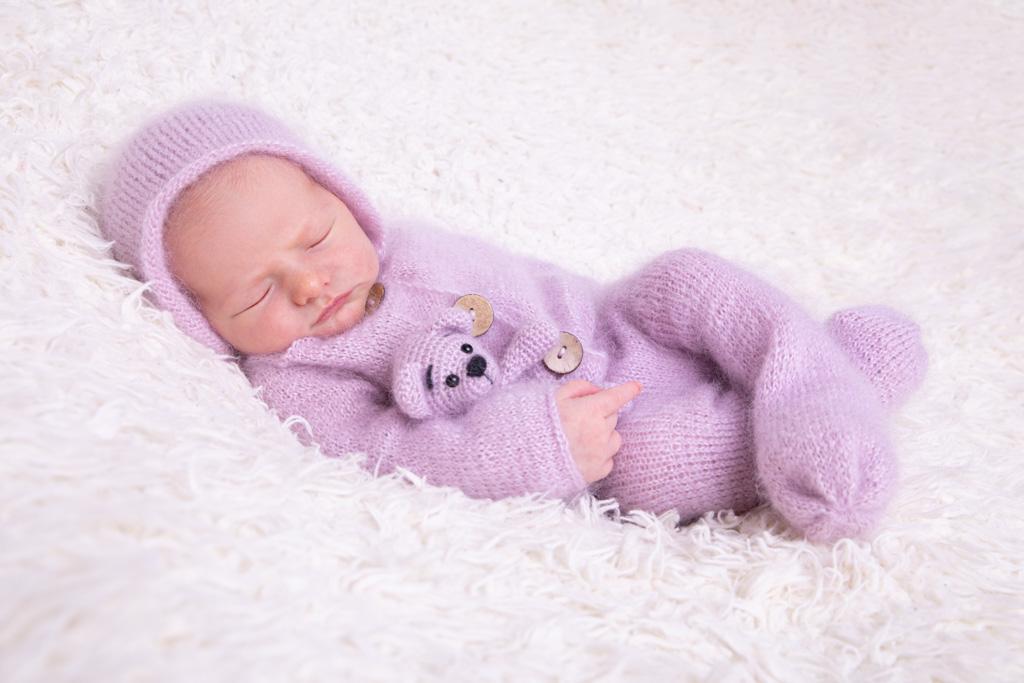 baby schläft auf creme farbenem Fell, trägt einen fliederfarben gestrickten Overall und hat einen teddy im arm, carina rosen, babyfotograf köln, in lohmar