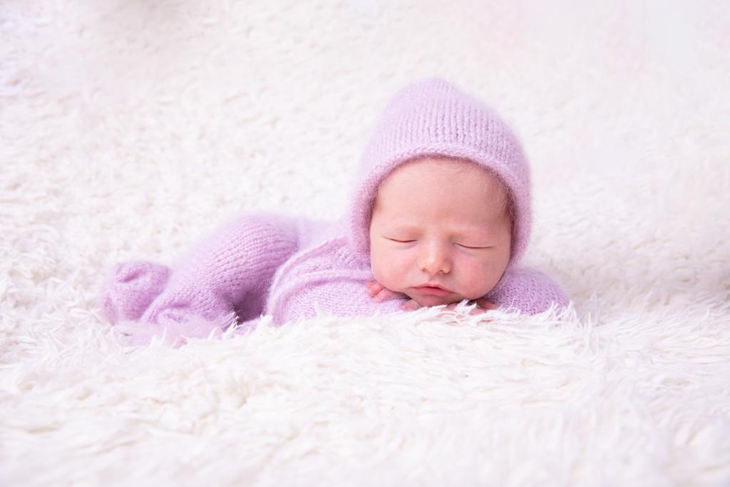 baby schläft auf creme farbenem Fell, trägt einen fliederfarben gestrickten Overall und liegt auf dem Bauch und hat den Kopf auf den Händen, carina rosen, babyfotograf köln, in lohmar