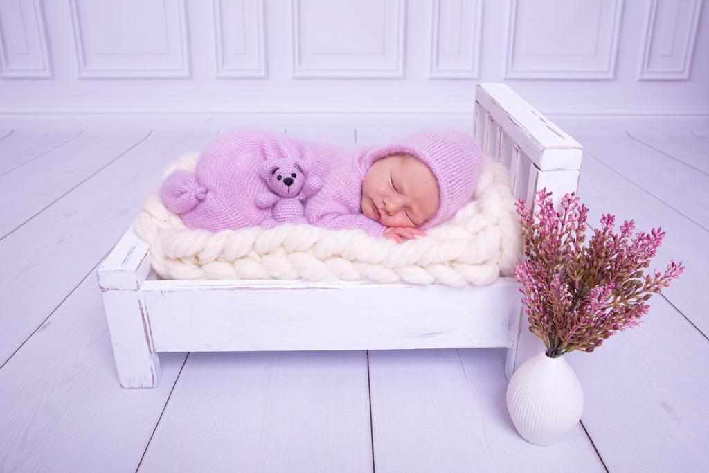 Neugeborenes liegt auf einem weißen Bett und schläft, ein teddy sitzt am bauch, neugeborenes koeln, carina rosen, bei overath