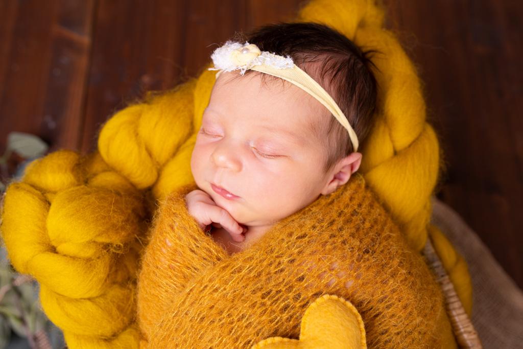 Baby in senfgelb mit der hand unter dem kinn