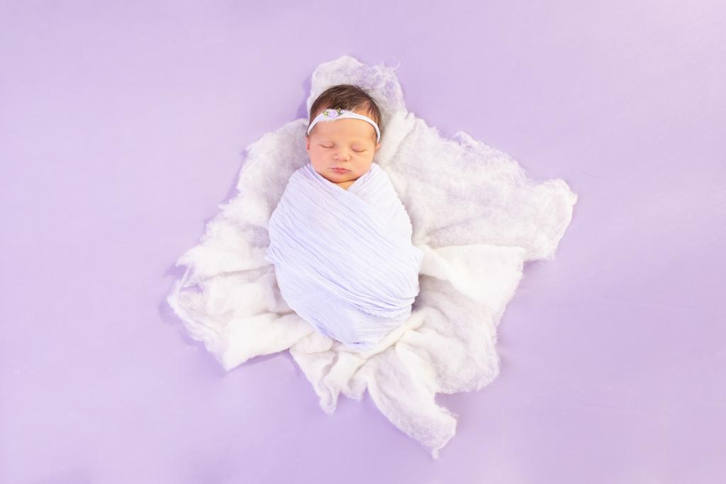 schlafendes baby gepuckt auf weißem Filz auf fliederfarbener Decke carina rosen fotografin für neugeborene