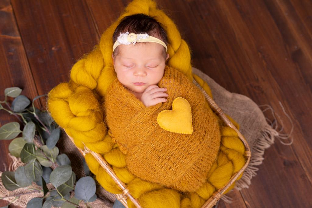 Neugeborenes Mädchen in senfgelb mit einem Herz auf der Brust