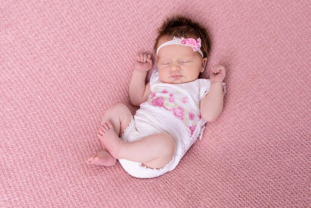 Baby in einem weissem Body mit rosenblüten darauf